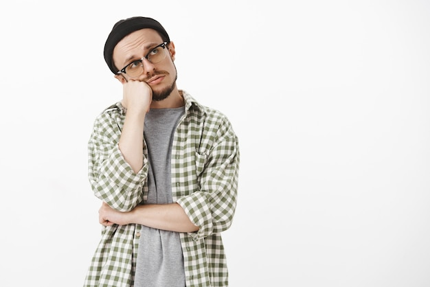Bored frustrated gloomy handsome bearded guy in glasses black beanie and checked green shirt leaning head on fist gazing at upper right corner with lonely indifferent look expressing apathy