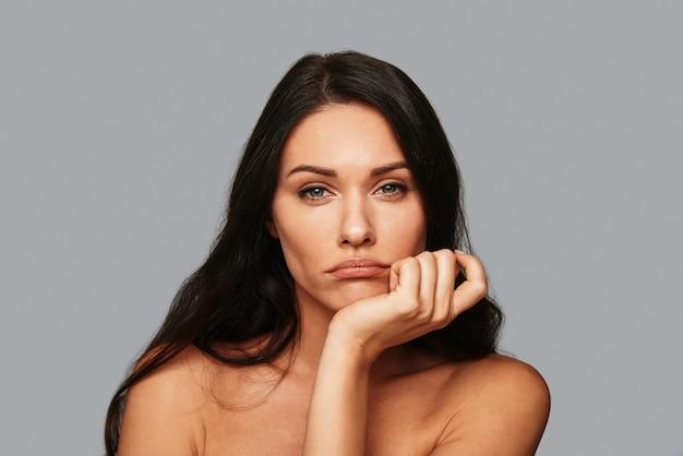 Скучающий. разочарованная молодая женщина смотрит в камеру, стоя на сером фоне