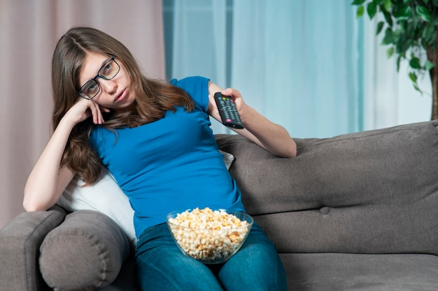 Скучающая девушка в очках молодая усталая женщина с скучным лицом сидит на диване или диване у себя дома в