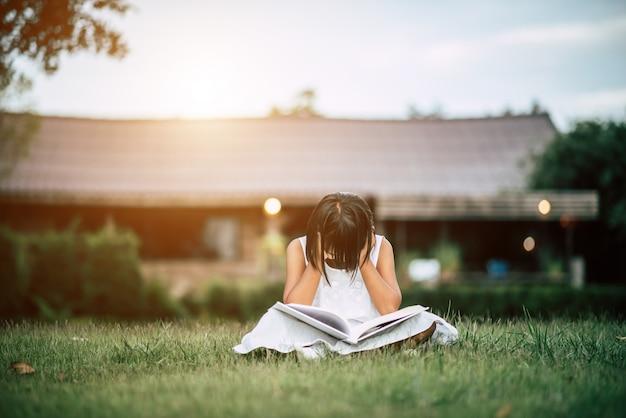 Скучающая девушка, читающая в саду