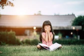 Bored girl reading in house garden