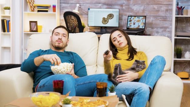 Скучающая девушка, сидящая на диване с котом на коленях и парнем рядом с ней, использует пульт от телевизора.