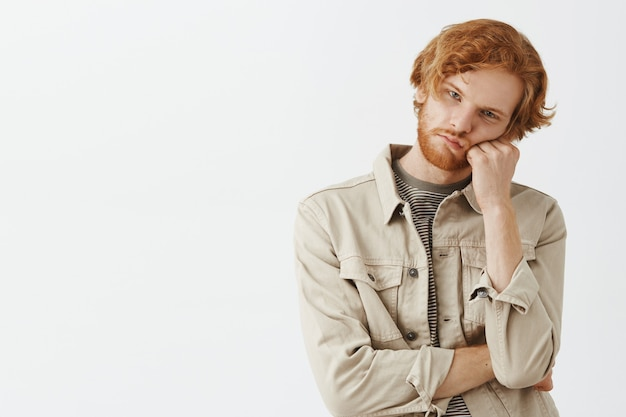 Bored and gloomy bearded redhead guy posing against the white wall