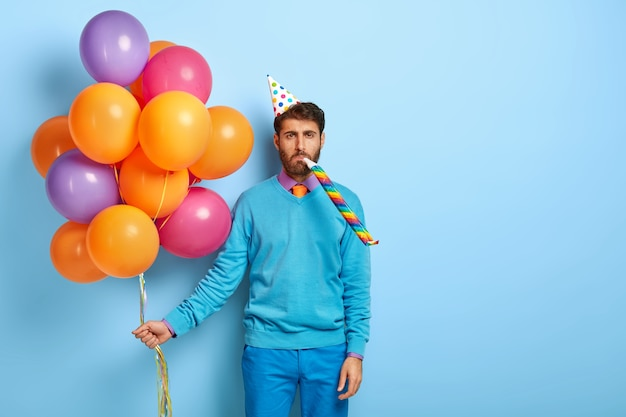 Bored guy with birthday hat and balloons posing in blue sweater