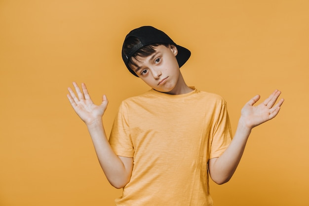 Bored handsome young boy dressed in yellow t-shirt and baseball cap spreads his hands out, being in doubt.