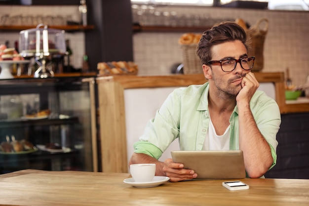 Bored hipster man using tablet computer