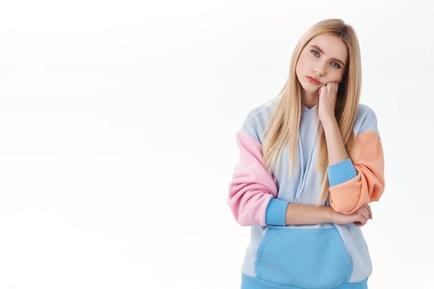 Скучно в доме. портрет равнодушной капризной белокурой девочки-подростка, носить толстовку с капюшоном