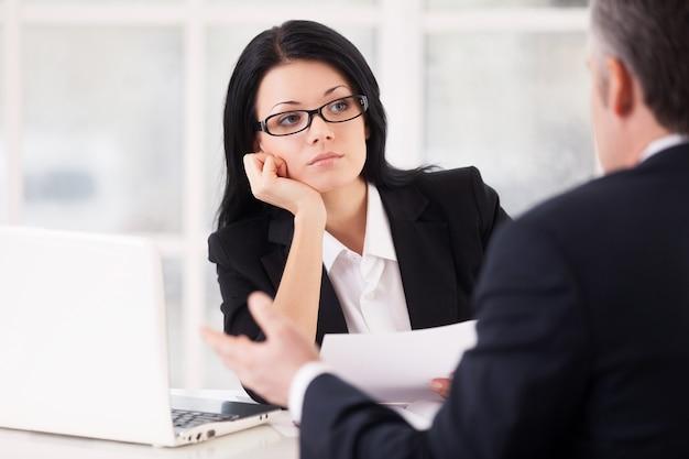 Скучающий интервьюер. скучающая молодая женщина в формальной одежде сидит за столом и держит голову в руке, в то время как седой мужчина сидит перед ней и жестикулирует