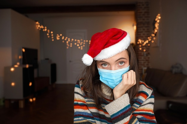 Скучающая дама в цветном пуловере и красной рождественской шляпе сидит в темной комнате с огнями и держит голову за руку дома