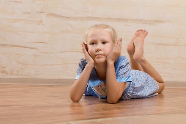 Скучно маленькая девочка, лежа на деревянном полу