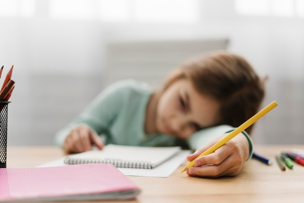 Bored little girl resting her head while doing her homework