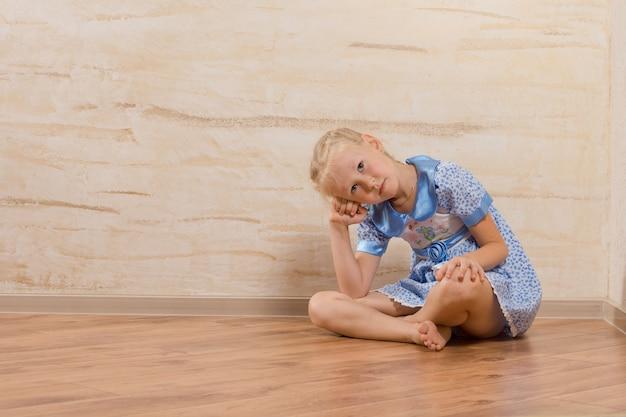 Скучно маленькая девочка сидит, смотрит и ждет