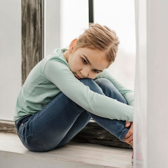 Bambina annoiata che si siede sul davanzale di una finestra