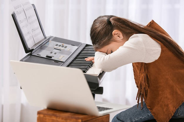 Bored little girl taking music lessons online at home