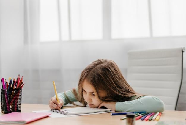 Bambina annoiata che prende appunti