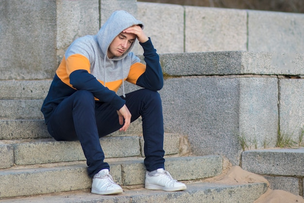 Bored lonely handsome guy sitting on stairs and holding his head with hand. frustrated yound sad upset man.