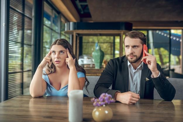 지루한 긴 머리 슬픈 여자와 의상을 입은 부주의 한 남자가 여름 카페에서 스마트 폰으로 이야기