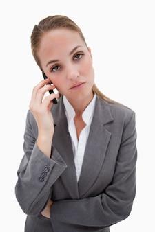 Скучно глядя сотрудник банка на своем мобильном телефоне