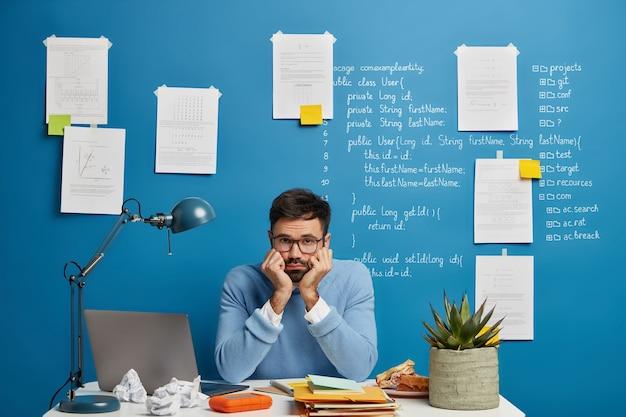 退屈した男性の学部生が仕事中に失敗または問題を抱えている