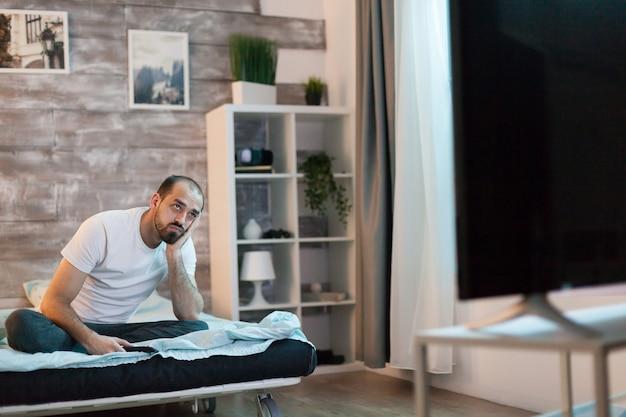 Скучающий человек переключает каналы по телевизору поздно ночью.