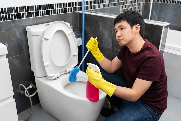退屈な男がトイレの便器を掃除する