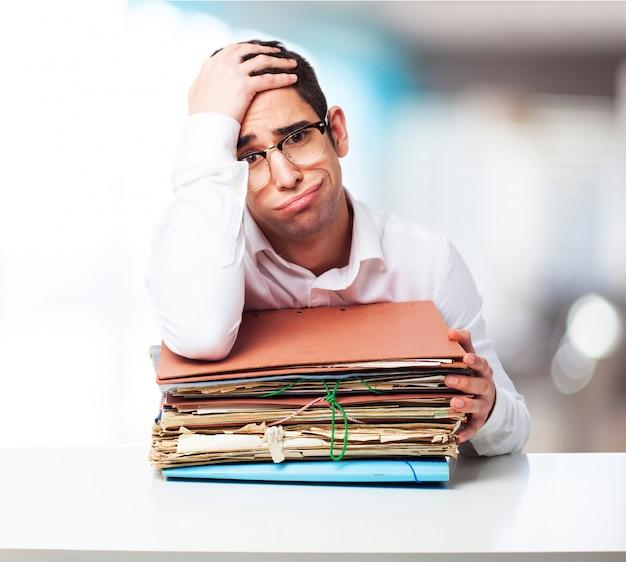 Скучающий человек смотрит на стопку бумаг с одной рукой на лбу