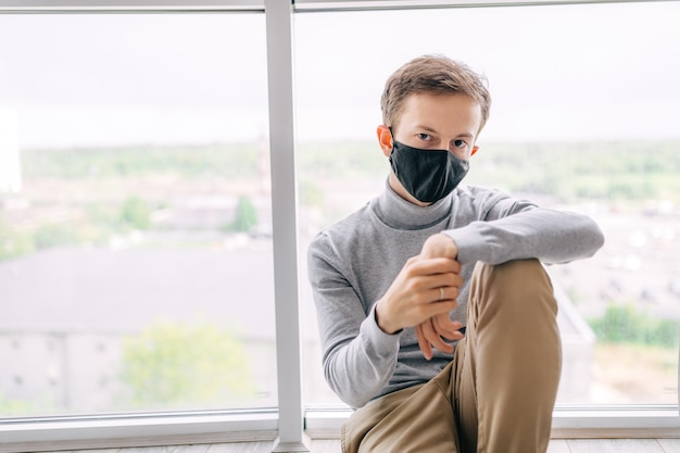 A bored man in quarantine wearing a medical mask sits at home and is bored.