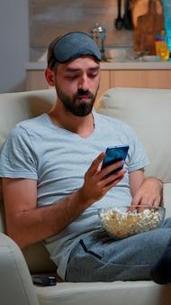 Скучно человек сидит на диване, держа миску попкорна