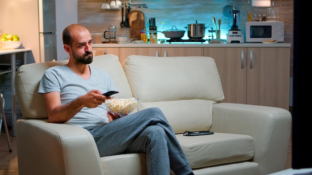 Bored man switching tv channels holding popcorn in hads