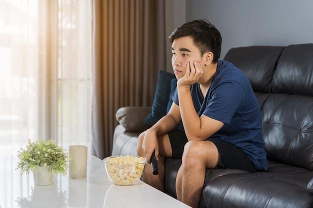 Скучающий человек смотрит телевизор и сидит на диване в гостиной