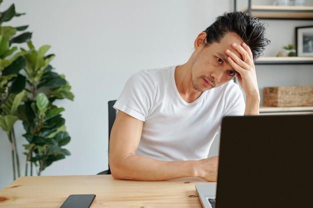 Скучающий человек работает на ноутбуке