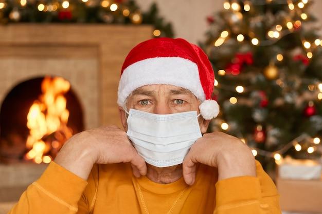 Скучающий зрелый мужчина сидит в гостиной с новогодним украшением, держа кулаки под подбородком, в медицинской защитной маске для предотвращения инфекции, желтой рубашке и шляпе санта-клауса.