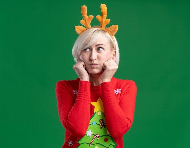 Скучающая блондинка средних лет в рождественской повязке на голову из оленьих рогов и рождественском свитере смотрит в сторону с надутыми щеками, держа руки на лице, изолированном на зеленом фоне