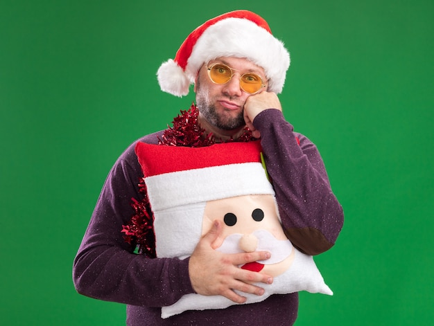 Bored middle-aged man wearing santa hat and tinsel garland around neck with glasses holding santa claus pillow  keeping hand on face isolated on green wall