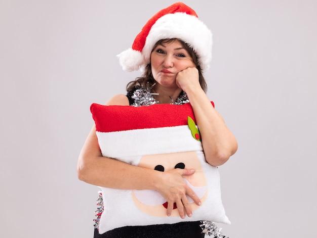 Скучающая женщина средних лет в шляпе санта-клауса и гирлянде из мишуры на шее, держащая подушку санта-клауса, глядя в камеру, держа руку на лице, пухлые щеки, изолированные на белом фоне с копией пространства