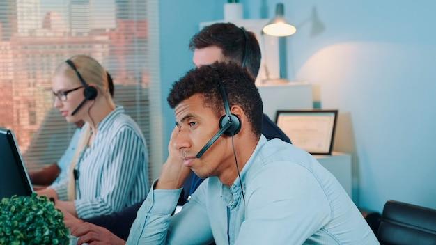 Скучающий многонациональный оператор службы поддержки клиентов ждет телефонного звонка от клиента