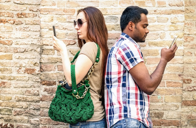 Bored multiracial couple using mobile smart phone