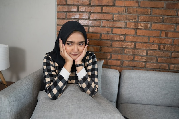 Bored muslim woman sitting on a couch