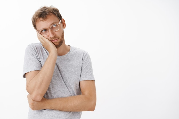 Bored nostalgic gloomy guy in transparent glasses with bristle leaning head on palm staring at upper right corner with jealousy and sadness feeling boredom over white wall