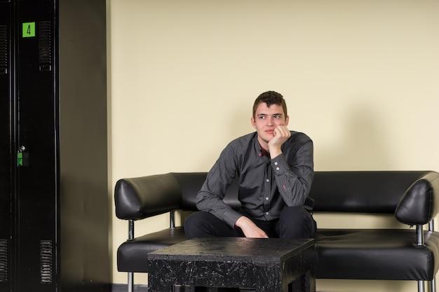 Скучающий или взволнованный мужчина, сидящий на современном черном кожаном диване в зале ожидания с подперев рукой подбородок, мрачно смотрящий в сторону