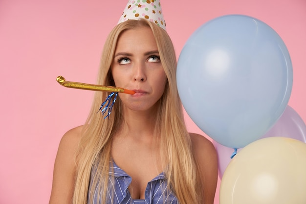 Bored pretty blonde woman with long hair rolling eyes and keeping party horn in her mouth, celebrating birthday with multicolored air balloons, being displeased with party, posing over pink background