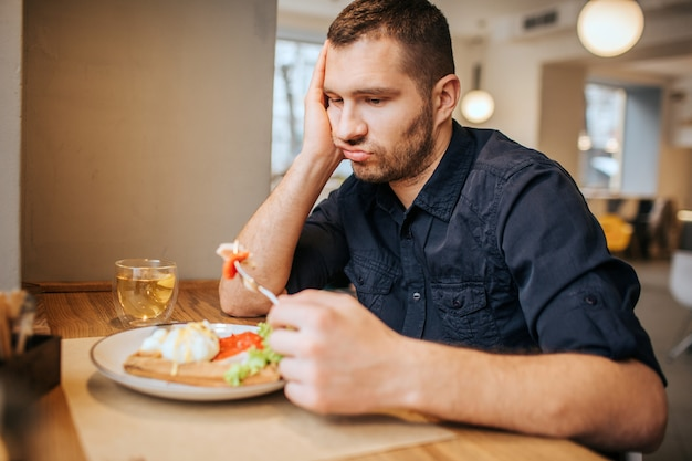 Bored and sad man is sitting at table and cafe. he is holding a piece of vegetable on fork. man is looking at it and breathing out.