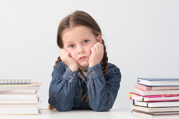 Bored schoolgirl sitting with head resting on hands, book stacks around.