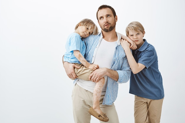 白斑のある小さな子供を抱えるカジュアルな服装で退屈な懐疑的なヨーロッパのお父さん、イライラや疲れからまぶたを転がす