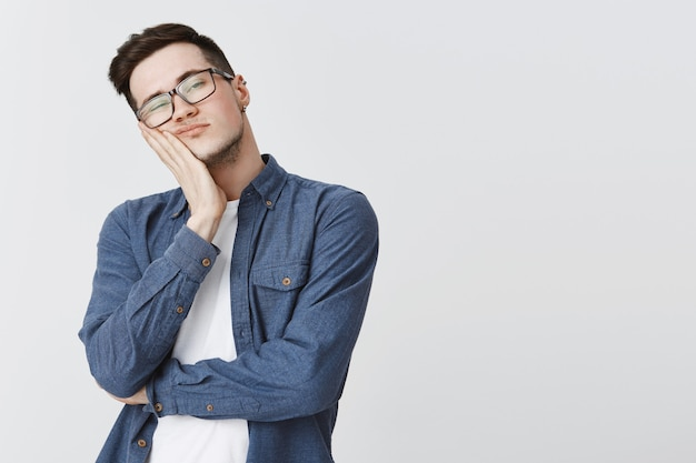 Bored student in glasses looking right reluctant, falling asleep
