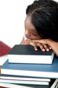 Bored student leaning on a stack of books