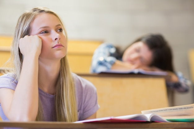 Bored student listening while classmate sleeping in university