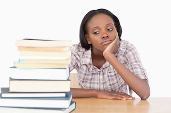 Bored student looking at a stack of books against a white background