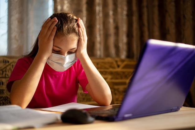 コンピューターで働く退屈学生。若い学校の学習者は自宅で勉強し、一日中インターネットを介して学習するのにうんざりして疲れています