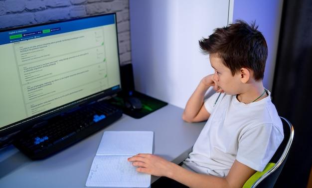 Скучно подросток учится на компьютере. делаем тесты. устали и скучно. учеба в карантине. школьник во время карантина